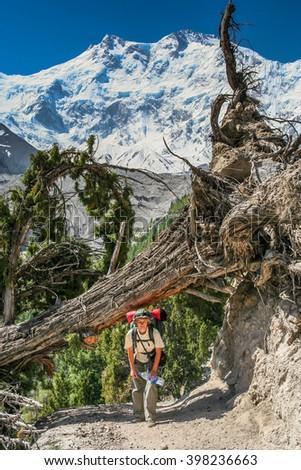 Woman walking up the stony mountain trail in Karakorum in Pakistan - stock photo