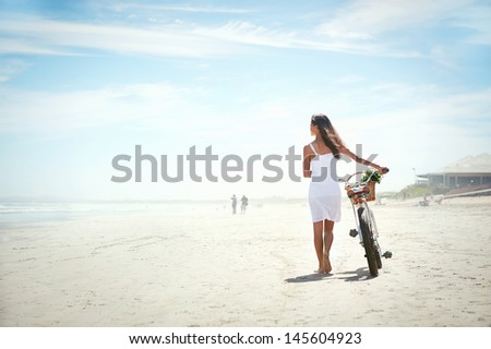Woman walking with bicycle along beach sand summer lifestyle carefree - stock photo