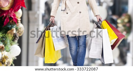 woman walking with shopping bags with christmas background. - stock photo