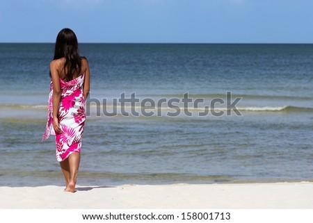 woman walks an empty beach - stock photo
