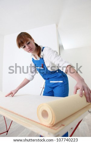 Woman wallpapering room - stock photo