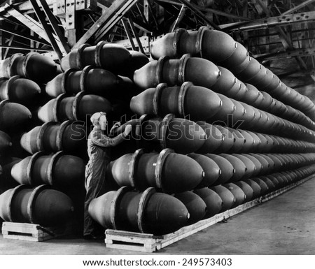 Woman war worker checks 1,000 lb. bomb cases loaded with explosives. Firestone Tire and Rubber Co., Omaha, Nebraska. May 1943 during World War 2. - stock photo