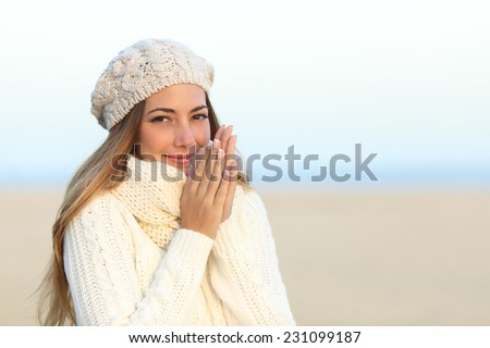 Woman warmly clothed in a cold winter on the beach with the sky in the background - stock photo