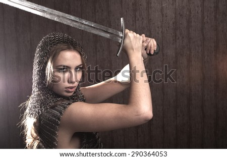 Woman warrior with sword in seductive armour looking at camera - stock photo