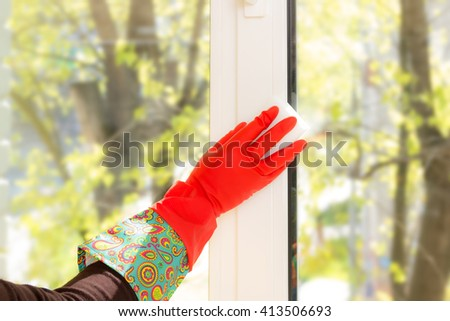 woman washes a window in the house. melamine sponge eraser. housewives. view from the window. window cleaning. beautiful gloves - stock photo