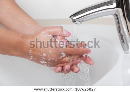 Woman washes her hands under the tap with soap - stock photo