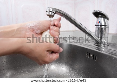 Woman washes her hands with soap - stock photo