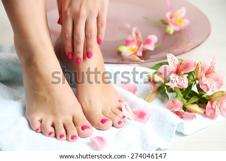 Woman washing beautiful legs in bowl, on light background. Spa procedure concept - stock photo