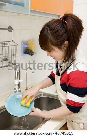 woman washing dishes in her kitchen - stock photo