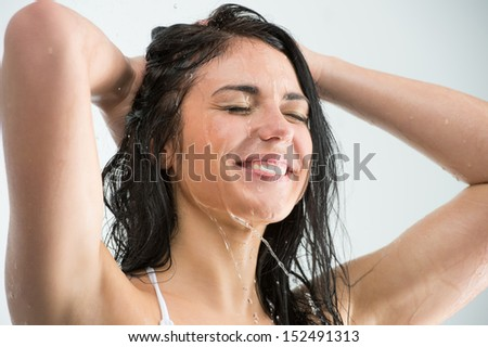 Woman washing her head while showering with happy smile and water splashing. Beautiful Caucasian female model home in shower cabin. - stock photo