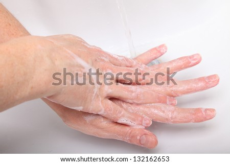 Woman washing sopas hands in bathroom white - stock photo