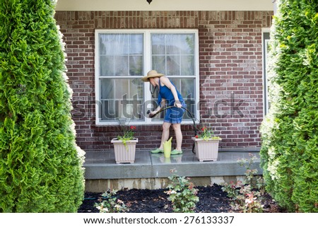 Woman washing the exterior windows of a house with an attachment on a hose as she cleans and refreshes the house after winter for the new spring season, view framed by two evergreen cypresses - stock photo