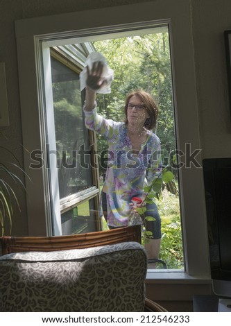 woman washing window from outside of house - stock photo