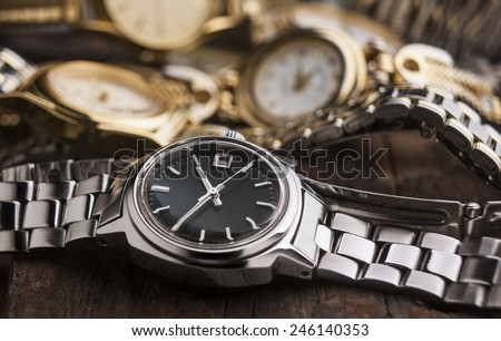 woman watches on wooden table - stock photo