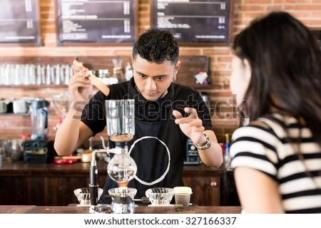 Woman watching barista preparing drip coffee in cafe - stock photo