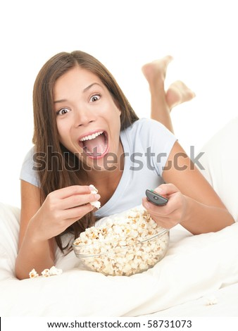 Woman watching funny movie on TV with shocked expression. Young beautiful female model eating popcorn having fun in bed. - stock photo