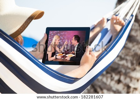 Woman watching movie on digital tablet while relaxing in hammock at beach - stock photo