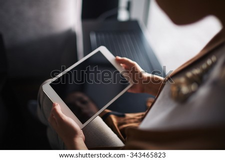 Woman watching something on her touchpad - stock photo