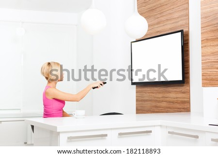 woman watching tv hold remote control changing channel, young girl in living room at home, isolated screen empty copy space - stock photo