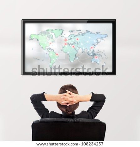 Woman watching tv. Photo from behind. Worldmap at the screen - stock photo