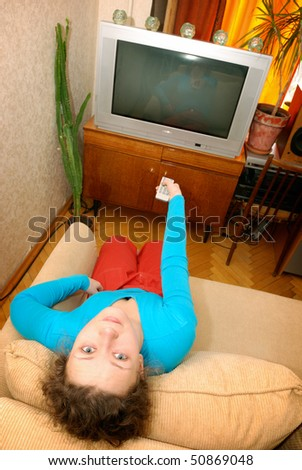 woman watching tv sitting on sofa - stock photo