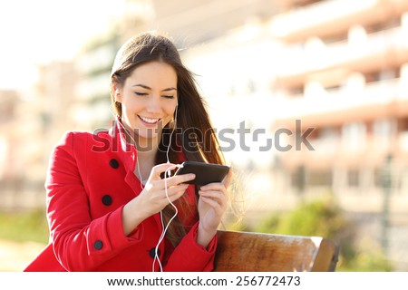 Woman watching videos in a smart phone with earphones sitting in a park with an unfocused buildings in the background - stock photo