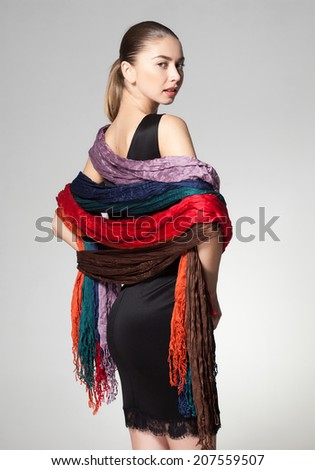 woman wearing a collection of scarves on grey background - stock photo