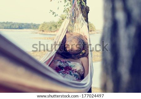 Woman wearing a dress with floral pattern and covering her face with a straw hat while relaxing in a hammock outdoors, in a warm day of summer, next to a sea and a green area. With retro effect. - stock photo