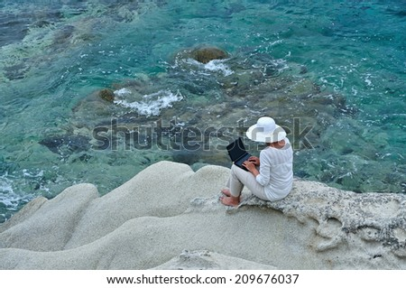 Woman wearing a hat sitting on the rock with laptop near the sea - stock photo