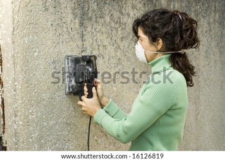 Woman wearing a paint mask uses an electric sander to sand a wall. Horizontally framed photo. - stock photo
