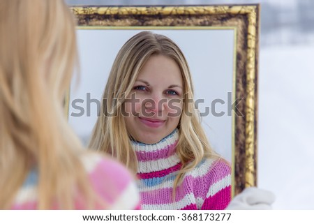Woman wearing a warm sweater and looking at her self in a mirror and smiling.  - stock photo