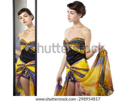 Woman wearing a yellow dress looking at her self in a mirror.  She is trying on a yellow dress and deciding on an outfit.  She looks fashionable and stylish. - stock photo