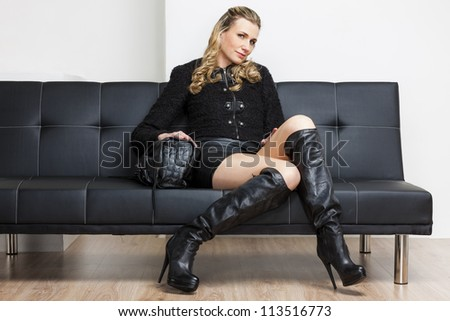woman wearing black clothes and boots sitting on sofa - stock photo