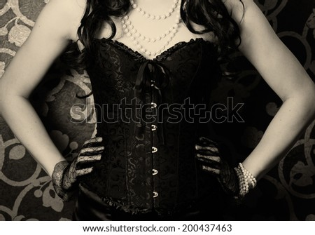 woman wearing black corset and pearls against retro background - stock photo