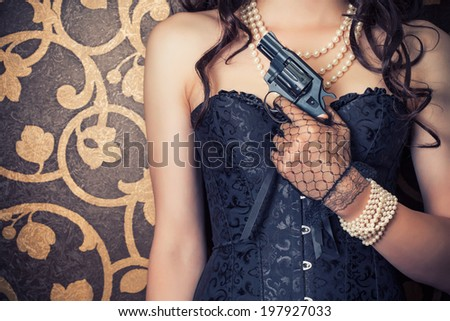 woman wearing black corset and pearls and holding a gun against retro background - stock photo