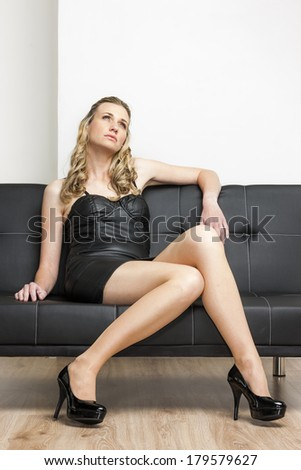 woman wearing black dress and pumps sitting on sofa - stock photo