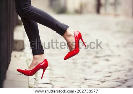 Woman wearing black leather pants and red high heel shoes in old town - stock photo