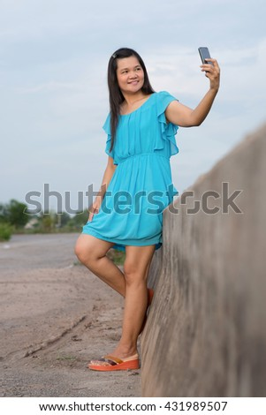 Woman wearing blue dress  taking self picture with mobile. - stock photo