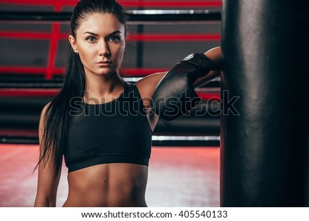 woman wearing boxing gloves near punching bag - stock photo
