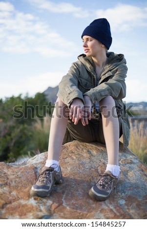 Woman wearing cap sitting on a rock looking away in the countryside - stock photo