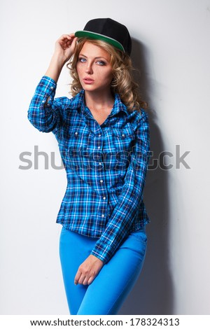 woman wearing cap standing near white wall - stock photo