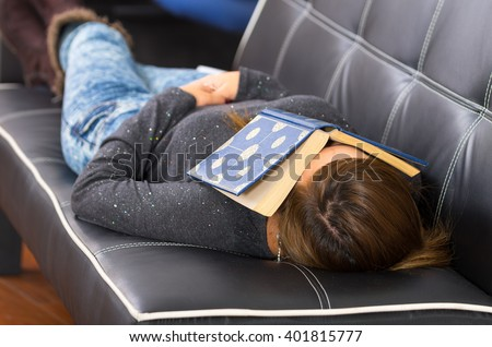 Woman wearing casual clothes lying comfortably sleeping on dark sofa with book covering face - stock photo
