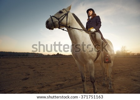 Woman wearing dressage costume riding a horse - stock photo