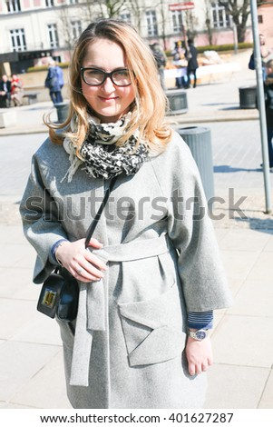 Woman wearing elegant grey coat and glasses. Autumn, cloudy day - stock photo