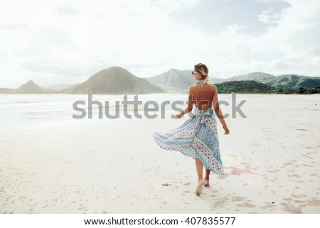 Woman wearing ethnic flying dress walking barefoot at the beach, Lombok, Indonesia - stock photo