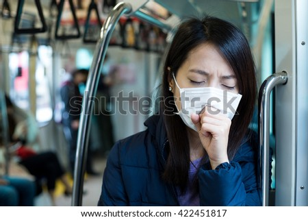 Woman wearing face mask in train compartment - stock photo