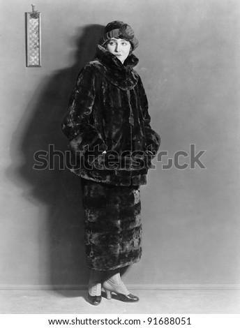 Woman wearing fur coat and skirt - stock photo