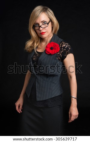 woman wearing glasses and a jacket looking at the camera with a serious expression - stock photo