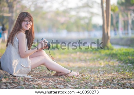 Woman wearing glasses holding a camera, sitting under a tree next dive. - stock photo