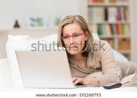 Woman wearing glasses lying on a sofa at home concentrating as she works on a laptop - stock photo